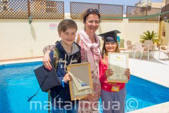 Una mamma con i suoi 2 bambini che hanno completato un corso di lingua