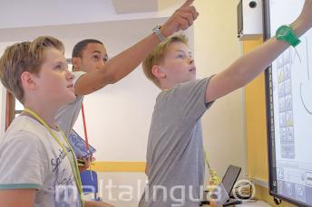 Un insegnante aiuta 2 studenti alla lavagna interattiva