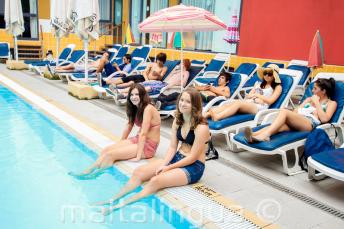 2 studenti con le gambe nell'acqua della piscina esterna del residence