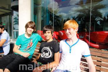 3 studenti seduti su una panchina fuori dal residence della scuola
