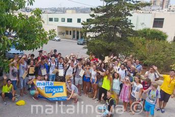Un gruppo di giovani studenti salutano fuori della scuola estiva