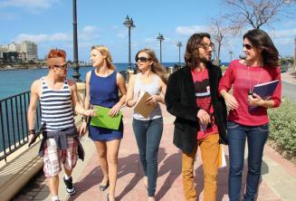 Gli studenti praticano inglese dopo le lezioni accanto a St Julians Bay, Malta