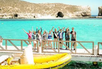Gli studenti salutano dalla barca ferma nella Blue Lagoon a Comino