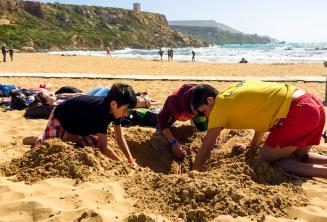 Gli animatori e i bambini giocano con la sabbia