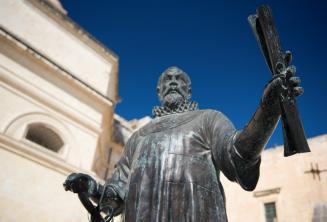 Una statua a Malta di un uomo che tiene un rotolo