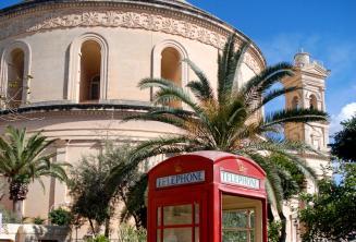 Una cabina telefonica rossa davanti alla chiesa di Mosta