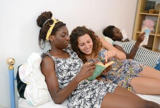 Uno studente legge di un libro con un membro della famiglia ospitante